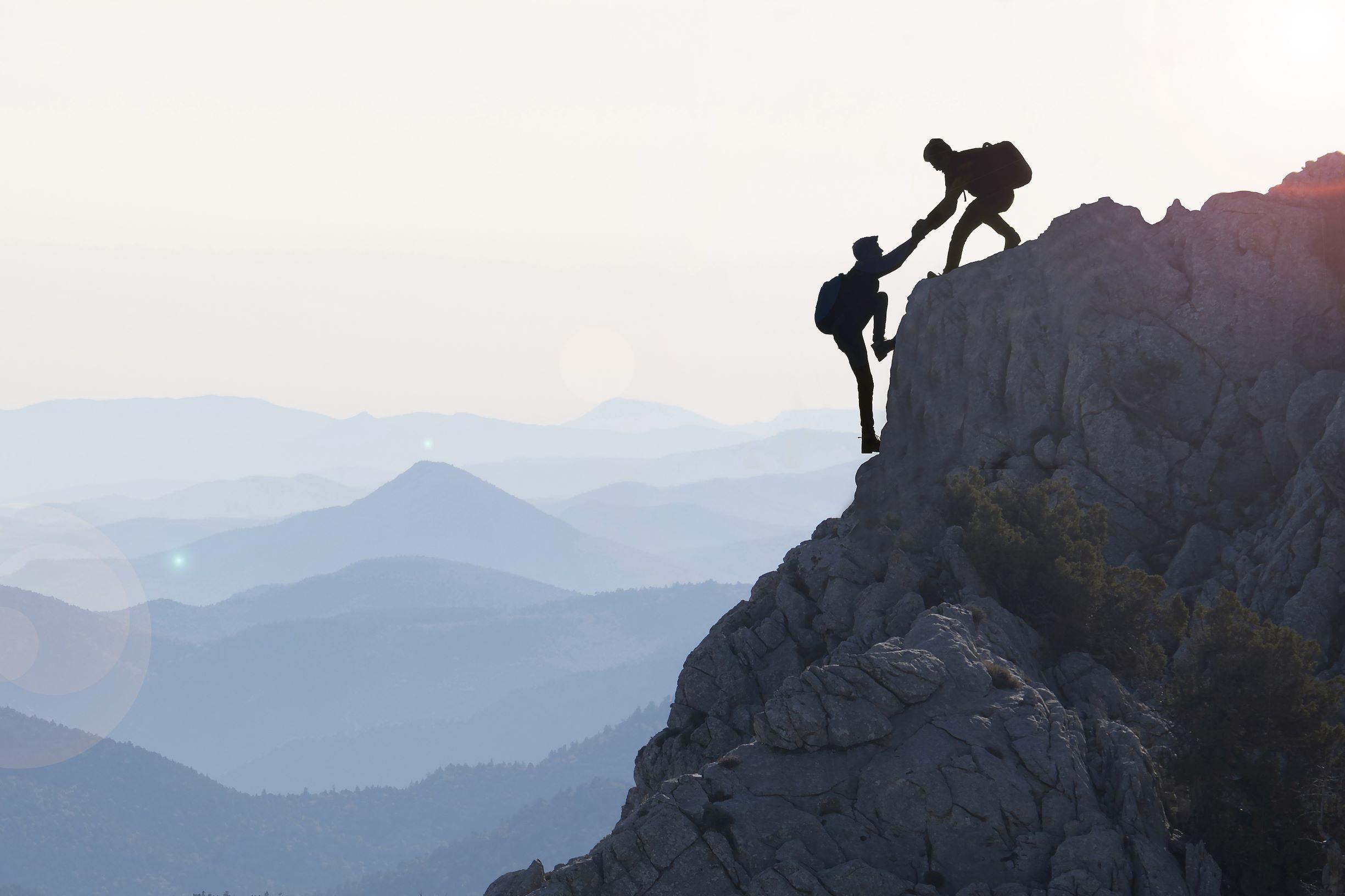 Ein Bergsteiger hilft seinem Freund bis auf die Spitze - LuArtX unterstuetzt Sie bis zum Erfolg